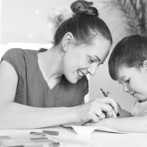 Horizontal shot of happy woman with hair bun, small boy, draw picture together, pose against domestic interior, have positive looks. Caring young mum spends free time with little son at home