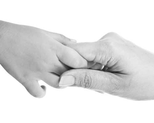 Closeup of giving a helping hand to another. isolated on white background